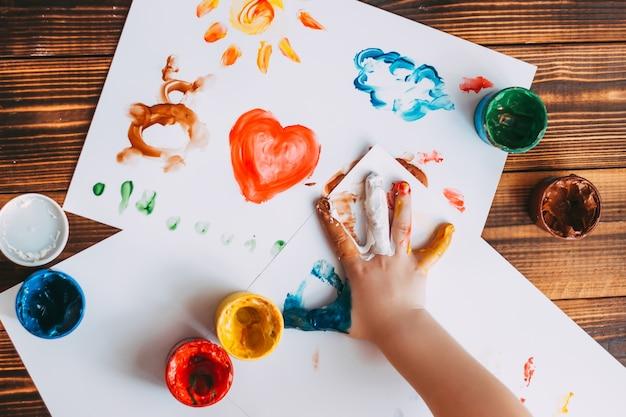Primo piano del mosaico colorato dipinto a mano del bambino il bambino sta disegnando il palmo della mano su fogli bianchi