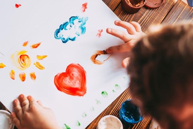 Primo piano delle mani del bambino che dipingono un mosaico colorato il bambino sta disegnando su fogli bianchi con vernici