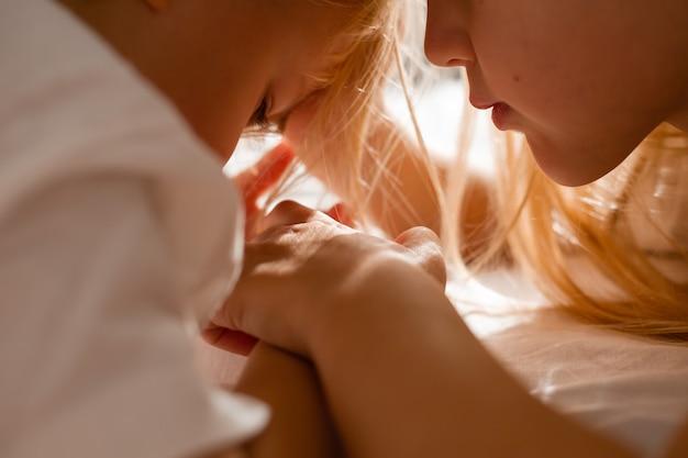 Primo piano di volti di bambini circondati da capelli bambini molto vicini che si tengono per mano