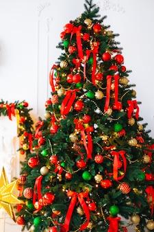 Un primo piano di un albero di natale decorato con fiocchi e palline rossi