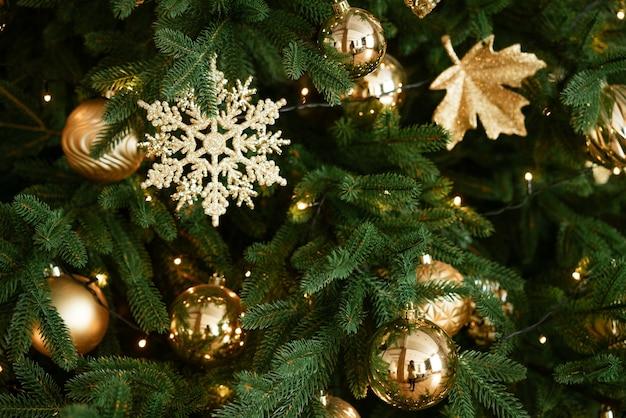 Primo piano dell'albero di natale con i giocattoli come concetto di fondo del fuoco molle della carta del nuovo anno