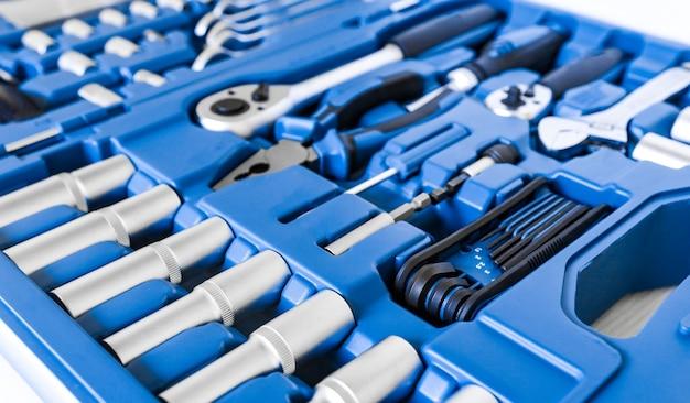 Primo piano di strumenti lucidi cromati in una riparazione e costruzione di una custodia blu