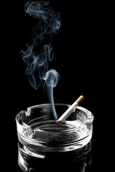 Primo piano della sigaretta sul posacenere con un filo di fumo