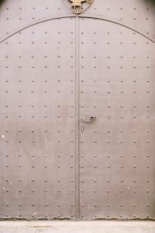 Primo piano di un cancello metallico chiuso a colori con motivo a rivetti