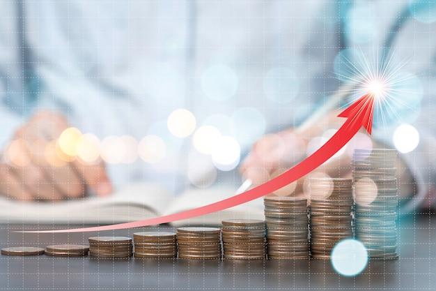Il primo piano conia l'impilamento con la freccia di aumento con il fondo dell'uomo d'affari. risparmio per il concetto di investimento.