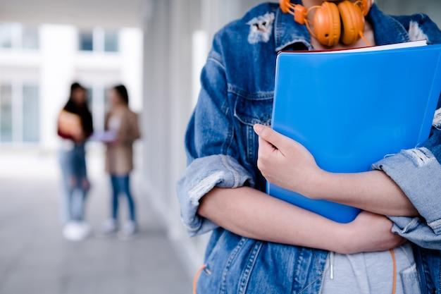 Primo piano di uno studente di college che tiene le cartelle mentre si trovava al concetto di educazione del corridoio