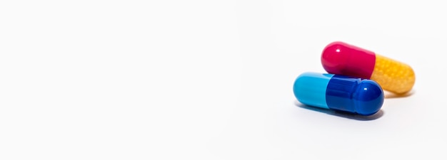 Pillola molle delle capsule della polvere variopinta del primo piano isolata sul supplemento giallo della medicina di rosa blu bianco