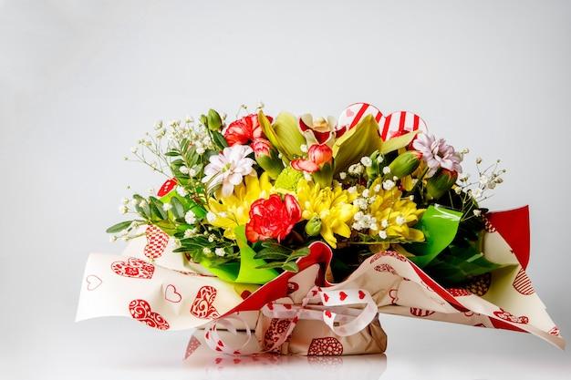Primo piano di coloratissimi fiori primaverili bouquet sul tavolo, bianco