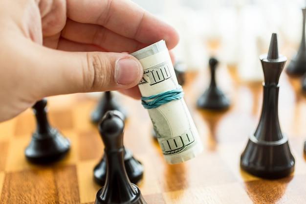 Uomo concettuale del primo piano che fa mossa al gioco di scacchi con le banconote in dollari?