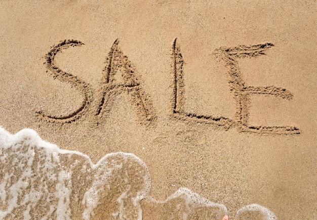 Foto concettuale del primo piano della vendita estiva scritta sulla spiaggia sabbiosa