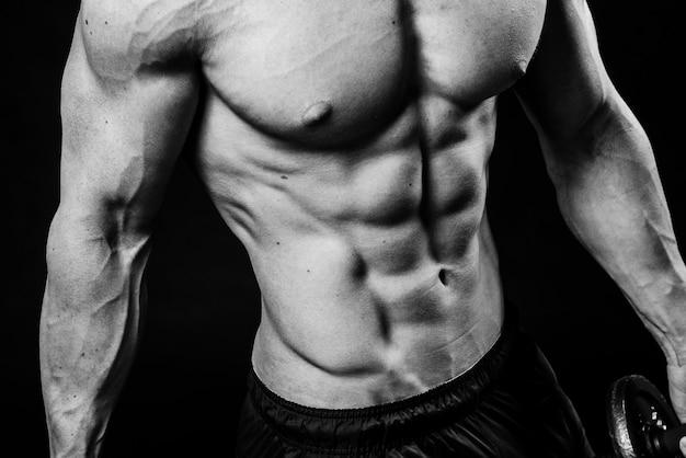 Primo piano del torso nudo sensuale forte sexy perfetto freddo con lo studio in bianco e nero del petto dei muscoli del pacchetto di 6 pettorali dell'abs, immagine orizzontale