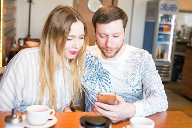 Primo piano delle coppie che ascoltano musica con il telefono cellulare al bar. musica d'ascolto della donna e dell'uomo con le cuffie.