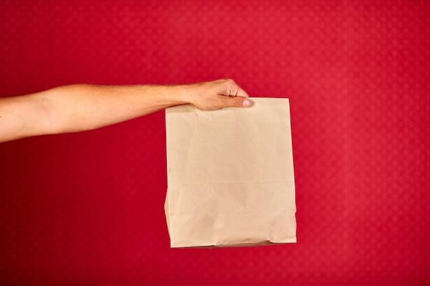 Primo piano della mano del corriere che tiene il sacchetto di carta della drogheria, servizio di consegna, colpo dello studio isolato