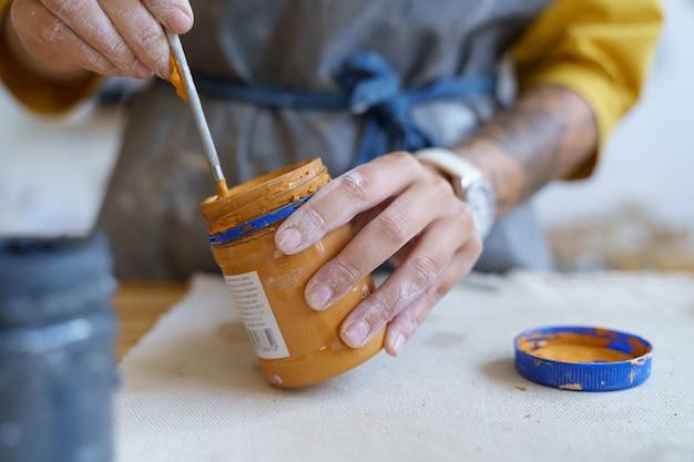Primo piano della mano dell'artigiana che tiene la vernice e il pennello che si preparano a decorare la ceramica fatta a mano