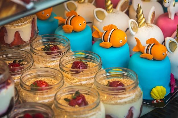 Primo piano di torta di mousse cremosa in vasetti decorati con fragole e torta per bambini con pesce e unicorni