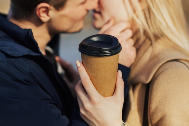 Closeup ritagliata ritratto di una coppia che tiene una tazza di bevanda calda in una giornata di sole e vuole baciare