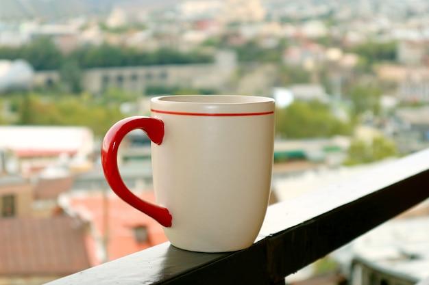 Primo piano una tazza di caffè sul balcone contro la vista sfocata della città