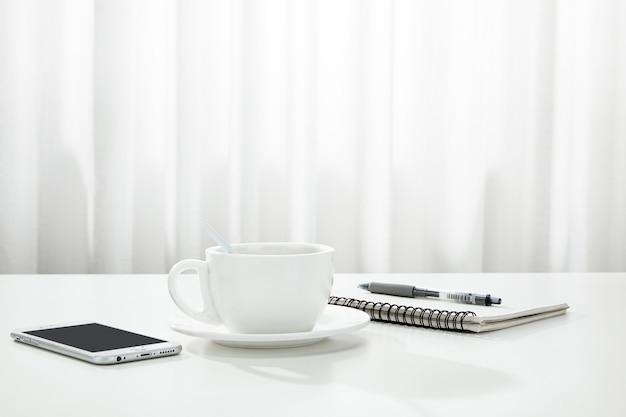 Primo piano di una tazza di caffè, un taccuino e una penna e uno smartphone su una scrivania bianca