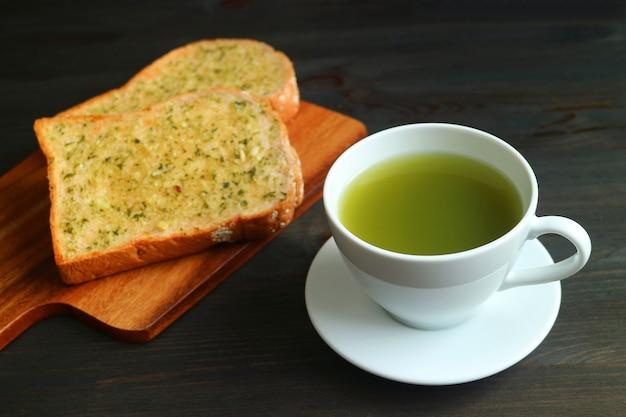Primo piano una tazza di tè verde caldo con toast di burro all'aglio sfocate sul tavolo di legno nero