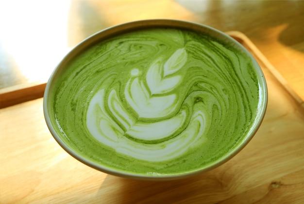 Primo piano una tazza di tè verde matcha caldo latte su un vassoio di legno