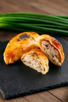 Primo piano sulla torta al forno piatto orientale tagliato con samsa di carne di pollo sulla lastra di pietra nera