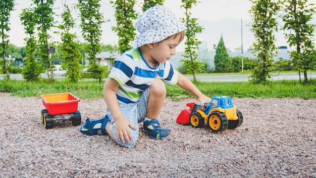 Primo piano del ragazzino sveglio che gioca sul terreno di gioco con i giocattoli. bambino che si diverte con camion, escavatore e rimorchio