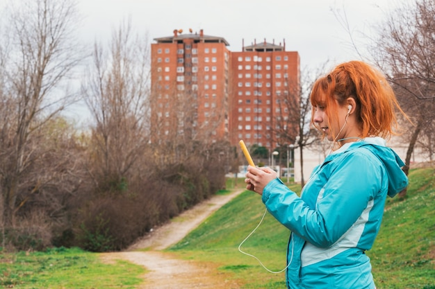Un primo piano di una femmina caucasica dai capelli rossi carina in abiti sportivi e cuffie guardando il suo telefono all'aperto con la città nel muro