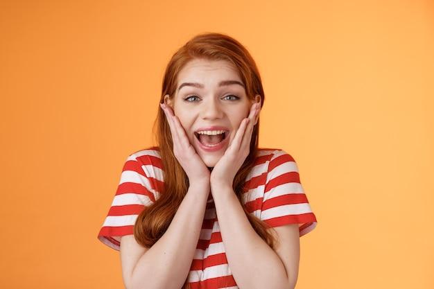 Primo piano carino rossa ragazza allegra sembra stupita urla di gioia fortunato ottenere il miglior punteggio ottenuto studioso...
