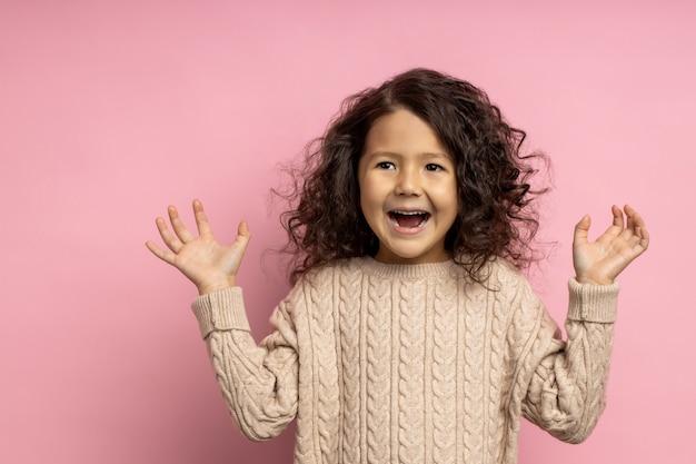 Primo piano della piccola ragazza bruna sorpresa sveglia con l'acconciatura riccia, alzando le mani con espressione eccitata e stupita, urlando di gioia