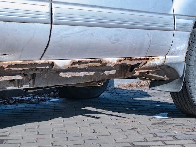 Primo piano del fondo dell'auto danneggiato dall'erosione dell'ossidazione della corrosione