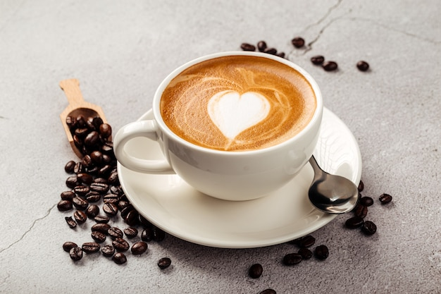 Primo piano sul caffè cappuccino decorato in una tazza bianca sullo sfondo di cemento