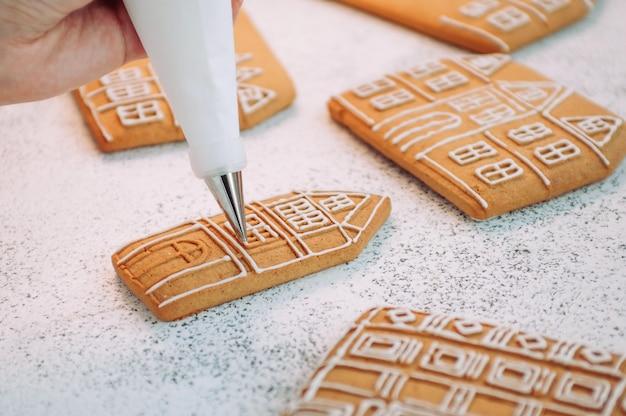 Primo piano di decorare la casa dei biscotti del pan di zenzero di natale. messa a fuoco selettiva sulla borsa per la glassa.