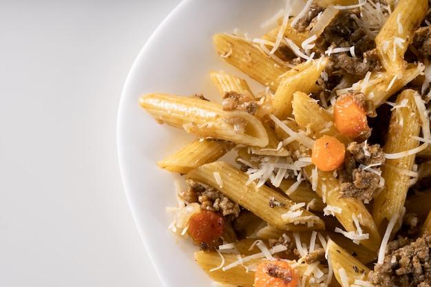 Primo piano di deliziosa pasta gourmet con condimento di carne e parmigiano sul piatto bianco