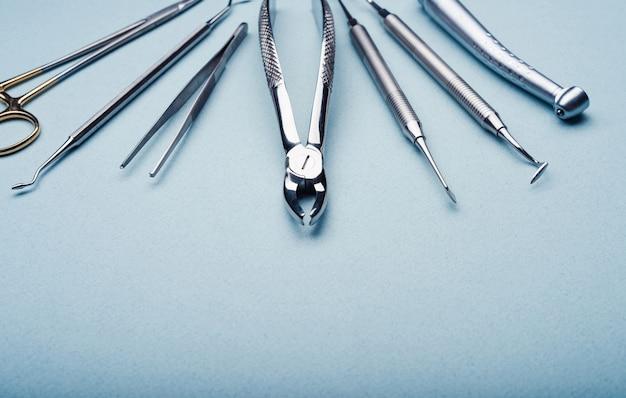 Primo piano degli strumenti dentali del metallo su fondo azzurro