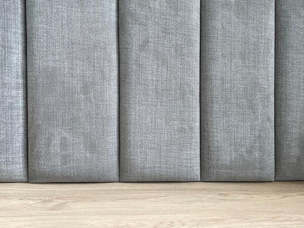 Particolare del primo piano della testiera con tessuto grigio.
