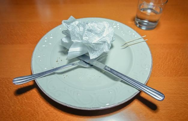 Primo piano del piatto sporco vuoto dopo aver mangiato con forchetta incrociata, coltello e tovagliolo usato sopra un tavolo di legno