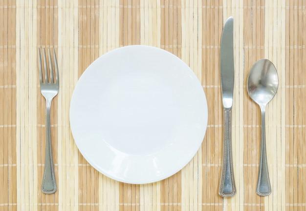 Piatto del primo piano con la forchetta e cucchiaio e coltello inossidabili sulla priorità bassa strutturata della stuoia