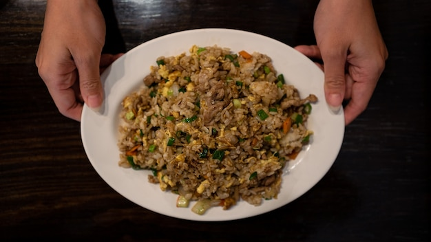 Primo piano che mangia un popolare riso fritto taiwanese con uova di maiale e verdure in un piatto bianco