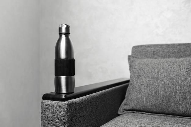 Primo piano della bottiglia di acciaio eco sul divano contro uno sfondo grigio testurizzato. foto in bianco e nero.