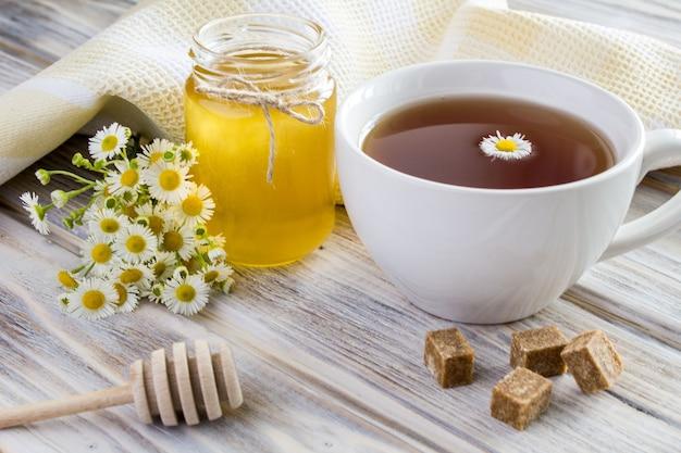 Primo piano su eea, miele e camomille sulla superficie in legno