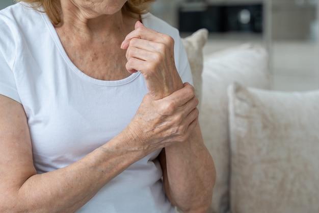 Donna anziana del primo piano che soffre di artrite delle mani seduta sul divano il concetto di