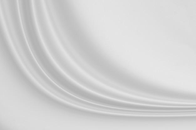Primo piano elegante stropicciato di tessuto di seta bianca sullo sfondo di stoffa e texture.