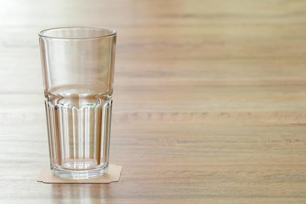 Primo piano di vetro vuoto sul tavolo di legno, il che significa un atteggiamento positivo verso qualcosa e pronto a imparare qualsiasi cosa