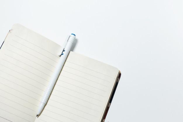 Primo piano del taccuino e della penna vuoti, isolati su fondo bianco.