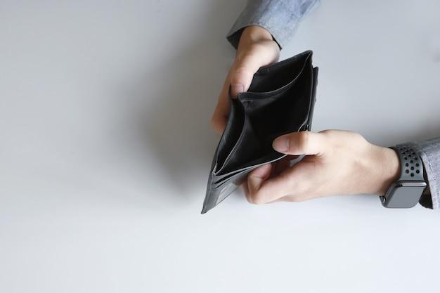 Portafoglio vuoto del primo piano senza soldi nelle mani di un uomo