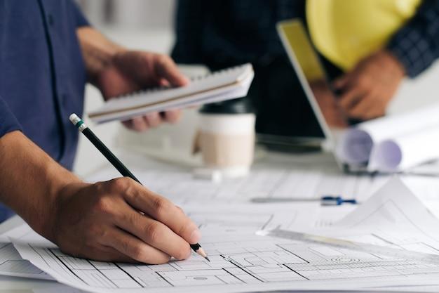 Primo piano del piano di disegno a mano dell'ingegnere su stampa blu con attrezzatura dell'architetto