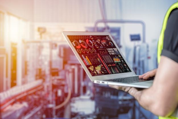 Ingegnere di primo piano che utilizza un computer portatile per monitorare e controllare i dati aziendali con sfocatura dello sfondo di fabbrica