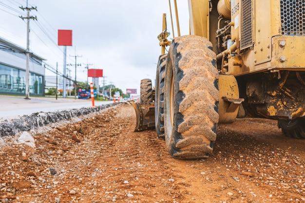 Escavatori del primo piano che rimuovono la pietra nei lavori di costruzione di una strada e di riparazione