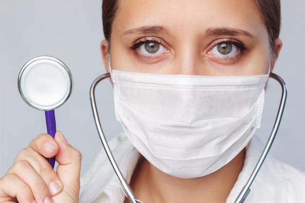 Primo piano del volto di una dottoressa con uno stetoscopio in una maschera medica su uno sfondo grigio