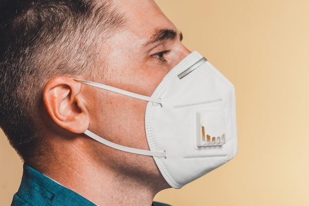 Primo piano del paziente di sesso maschile con visiera protettiva per auto isolamento durante la pandemia di coronavirus 2021